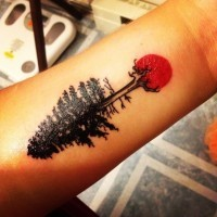 Tiny black ink tree tattoo on forearm with red sun