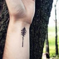 Tiny black ink tree tattoo on wrist