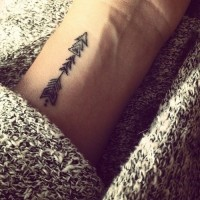 Tiny black ink tribal antic arrow tattoo on wrist