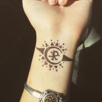 Tiny black ink wrist tattoo of sun shaped symbol