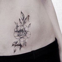Tiny blackwork style belly tattoo of flower painted by Zihwa