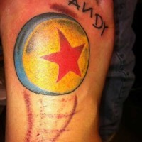 Tiny colored little ball tattoo on foot stylized with star and lettering