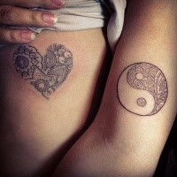 Tiny heart shaped and Yin Yang symbol shaped tattoo of side and arm stylized with ornamental flowers