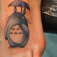 Tiny old cartoon like colored funny creature with umbrella tattoo on foot
