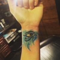 Tiny watercolor like wrist tattoo of Eye of Horus symbol