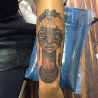 Tribal style colored forearm tattoo of tribal woman with jewelry