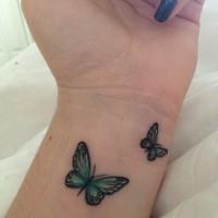 due piccoli farfalle tatuaggio su polso di ragazza