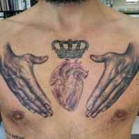 Typical colored chest tattoo of human hands with heart and crown