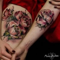 Typical colored forearm and feather tattoo of various roses