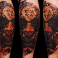 Typical illustrative style colored arm tattoo of demonic face with star shaped symbol
