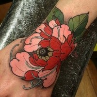 Typical new school style wrist tattoo of large flower with feather