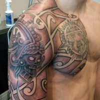 Typical tribal tattoo on chest and shoulder with various sculptures