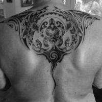 Unbelievable black ink ray tattoo on upper back stylized with Polynesian ornaments