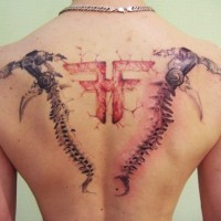 Unbelievable multicolored upper back tattoo of mystical symbol and bone like weapons