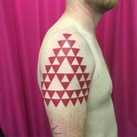 Unique big red colored symbol made from red triangles tattoo on shoulder