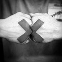 Ungewöhnliches schwarzes Kreuz  Tattoo auf Fäusten