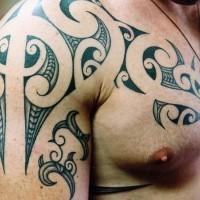 Unusual black tribal irish tattoo on shoulder