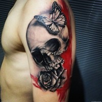 insolito combinazione dettagliato grande cranio con fiore e farfalle tatuaggio su spalla