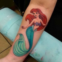Usual colored little cartoon forearm tattoo of Ariel mermaid