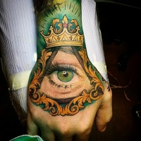 Usual illustrative style colored hand tattoo of human eye in pyramid and crown