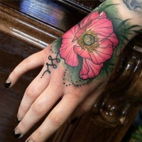 Usual painted pink colored natural looking flower tattoo on hand
