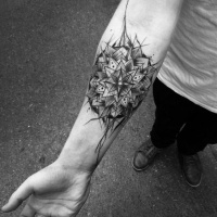 Very beautiful black ink flower tattoo sketch painted by Inez Janiak on forearm