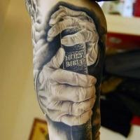 Sehr detailliertes realistisch aussehendes religiöses Arm Tattoo mit Händen, die Bibel halten