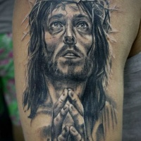 Very realistic and dramatic black and white praying Jesus tattoo on shoulder