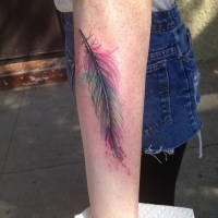 Very realistic detailed multicolored little feather tattoo on arm