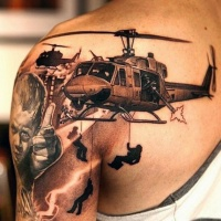 Very realistic looking black and white military helicopters tattoo on shoulder