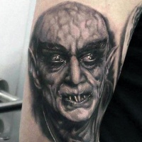 Very realistic looking black ink old horror movie hero tattoo on arm