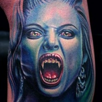 Very realistic looking colored evil vampire woman tattoo on leg