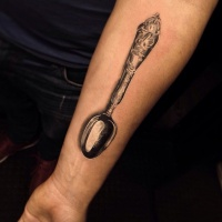 Very realistic looking detailed forearm tattoo of antic spoon