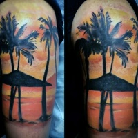 Very romantic looking colored ocean sunset with palm trees shoulder tattoo