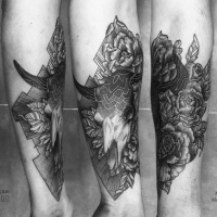 Vintage style black ink animal skull tattoo on forearm combined with various flowers