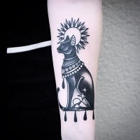 Vintage style black ink Egypt cat tattoo on forearm with sun ad stars