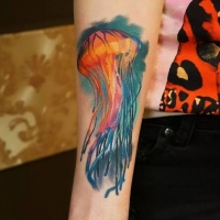 Vivid colors jellyfish in ocean forearm tattoo