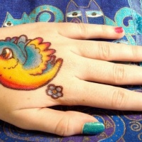 Vivid colors little bird tattoo on hand