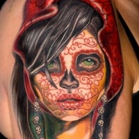 Vivid colors santa muerte girl with a red pattern on face tattoo on shoulder