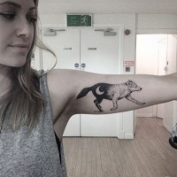 Walking wolf decorated with new Moon black and white tattoo on lady's biceps