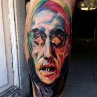 Watercolor like abstract vampire face tattoo on leg