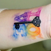 Watercolor love with black key tattoo on wrist