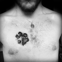 Watercolor style black ink chest tattoo of dog paw print