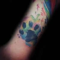 Watercolor style colored arm tattoo of small animal paw print