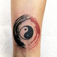 Watercolor style colored forearm tattoo of Yin Yang symbol