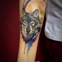 Watercolor style colored forearm tattoo of wolf with moon