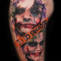 Watercolor style colored thigh tattoo of Joker face with lettering