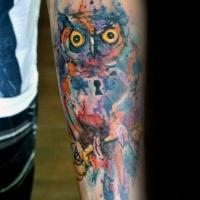Tatuaje de antebrazo estilo acuarela de búho estilizado con ojo de cerradura