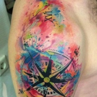 Watercolor style interesting looking colored shoulder tattoo of of nautical compass and date
