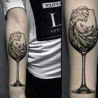 Schwimmender Wal im Wasser Wellen in Weinglas schwarzes und weißes Unterarm Tattoo im surrealistischen Stil